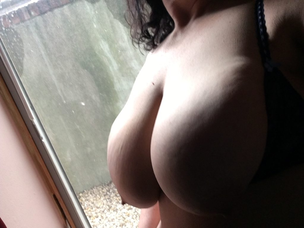 Sandy stands before a window with breasts exposed