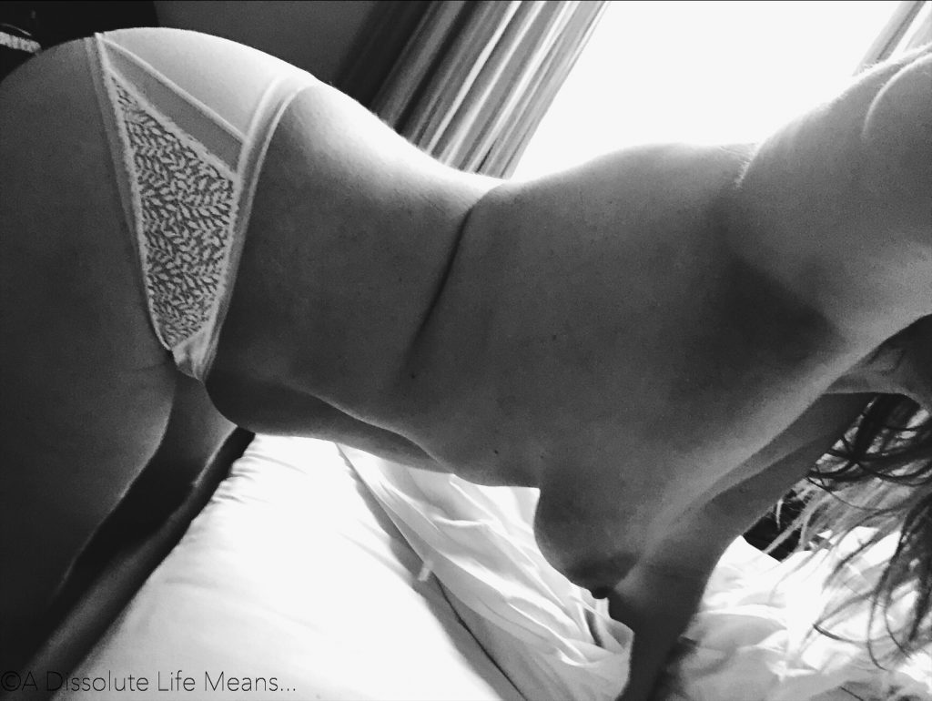 Black and white photo of Hyacinth leaning over a white bed in only her white lace underwear